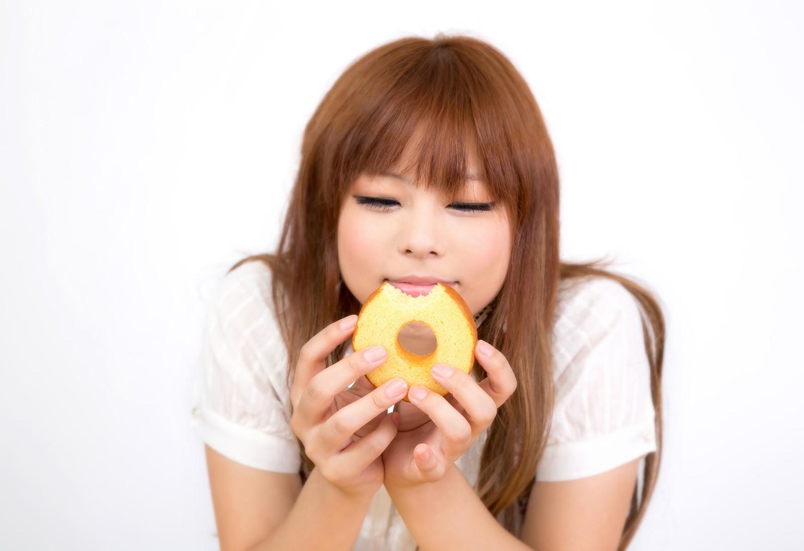 茶髪の女性がドーナツを食べている