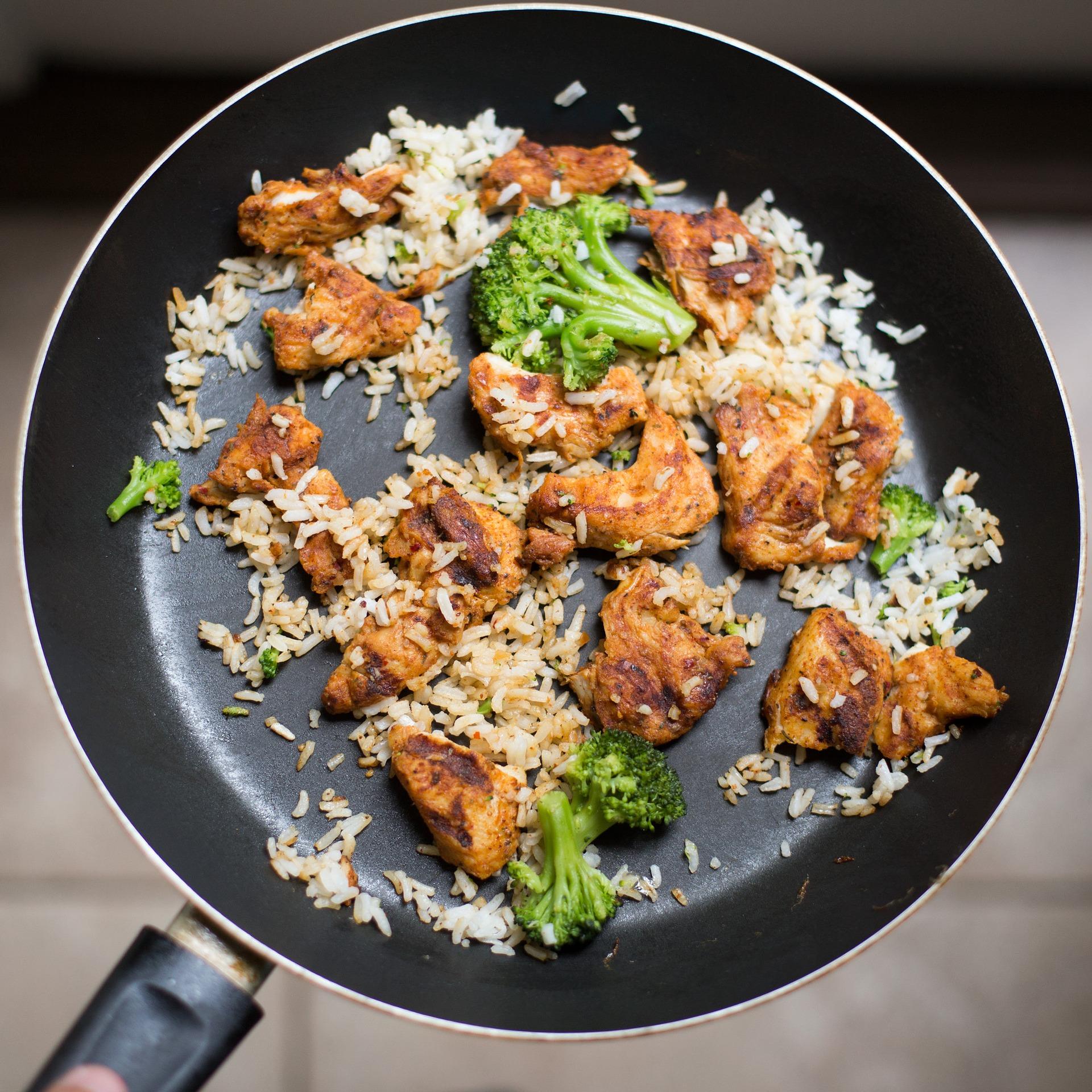 フライパンで炒める野菜と肉と米