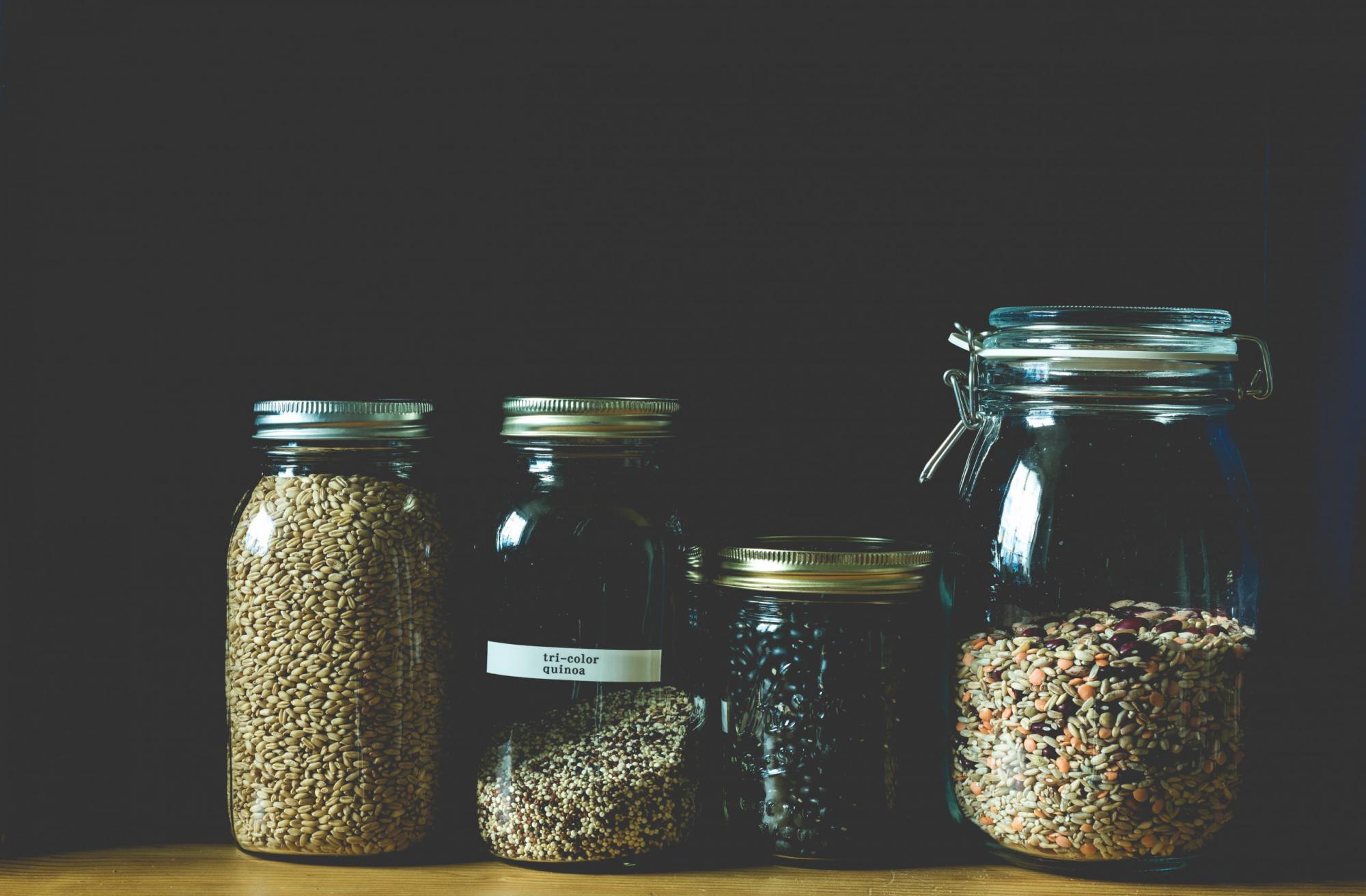 黒い背景と種が入った4つの小瓶