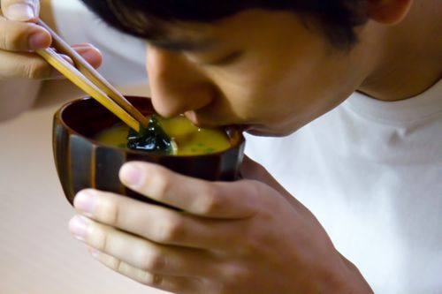お味噌汁をすする男性