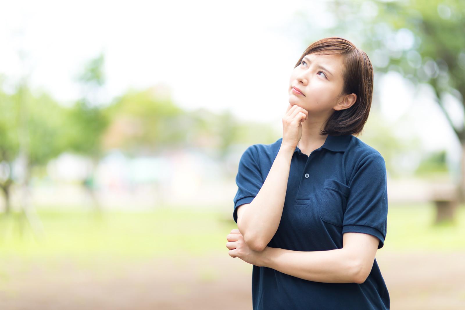 空を見ながら悩む若い女性