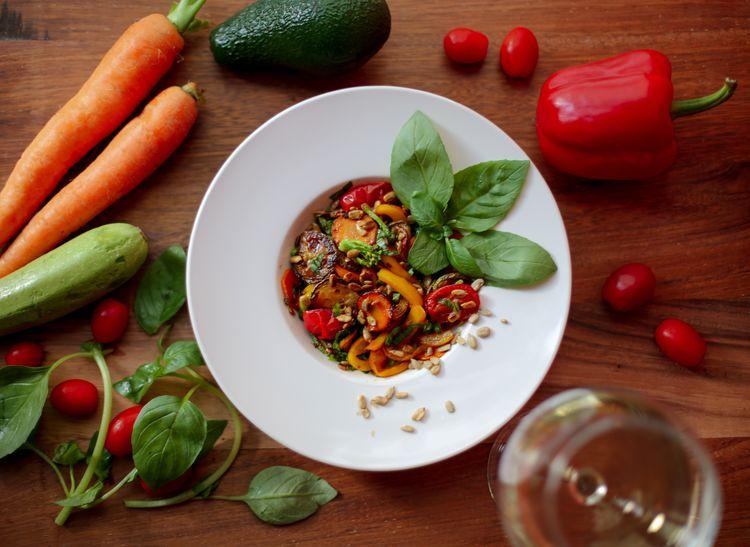 赤や緑の野菜の中心にある皿