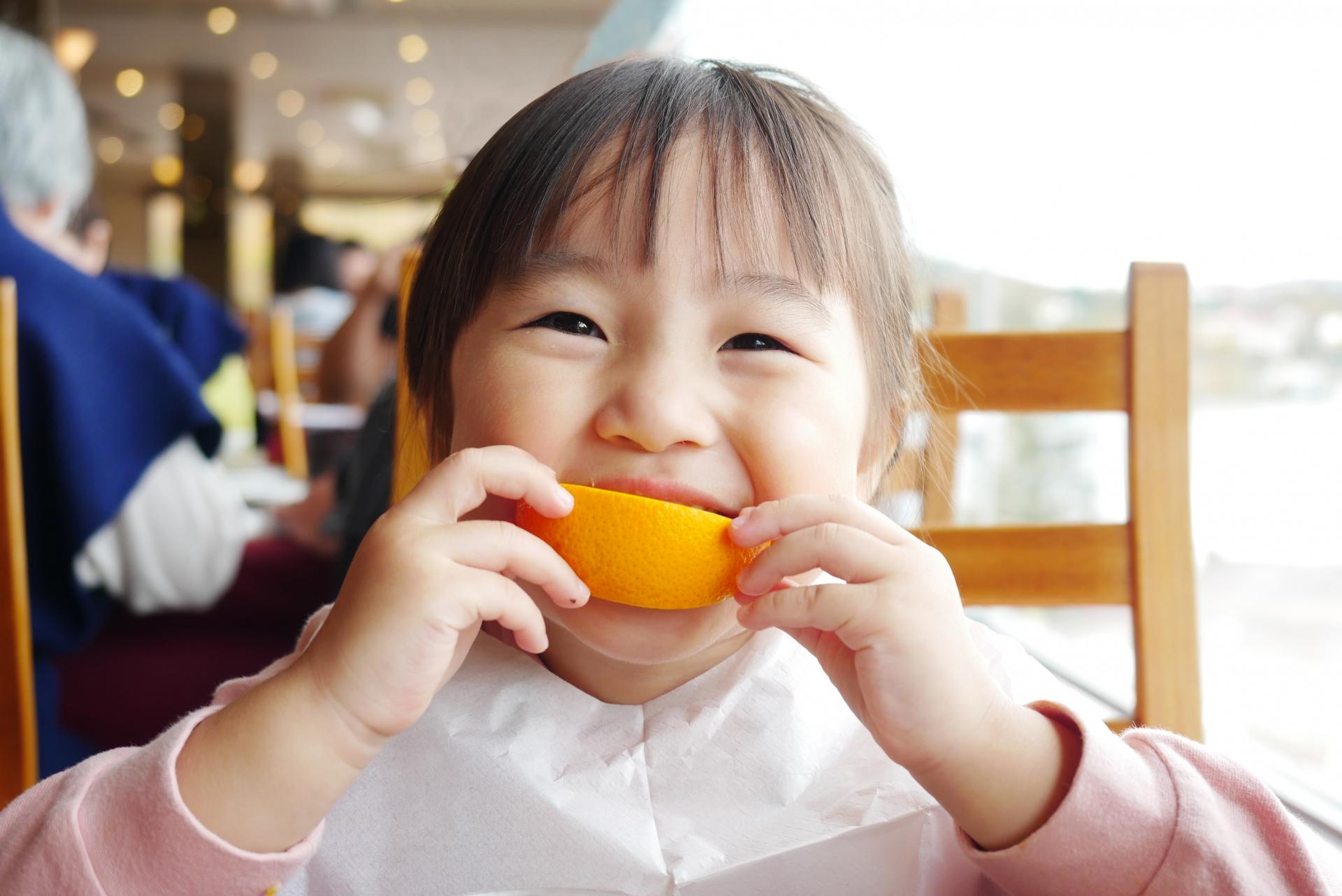 オレンジを頬張る女の子