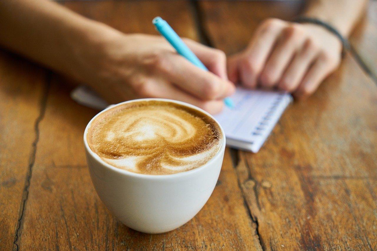 仕事でメモをとりながらコーヒーを飲む人