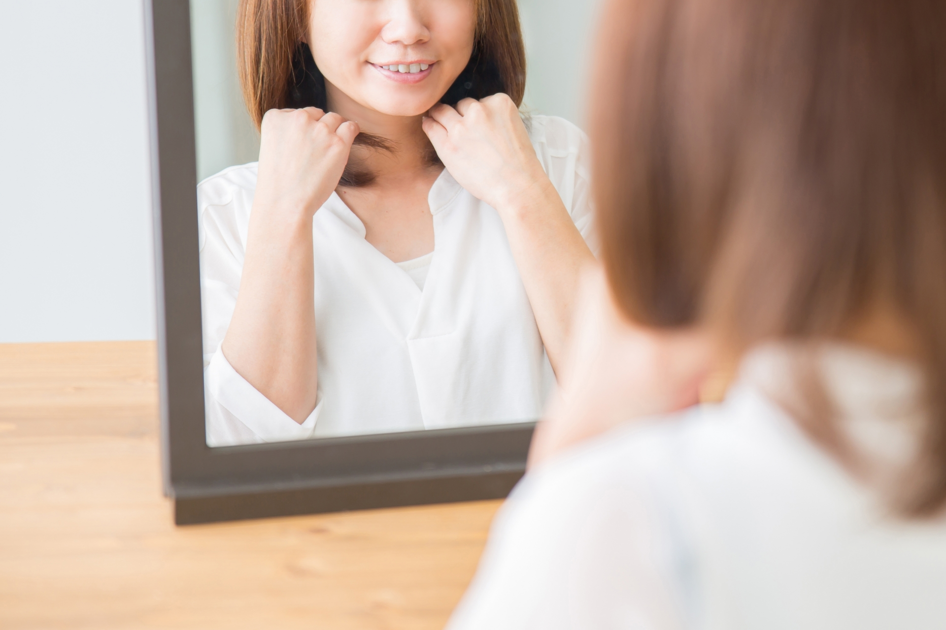 髪を整えながら微笑む女性