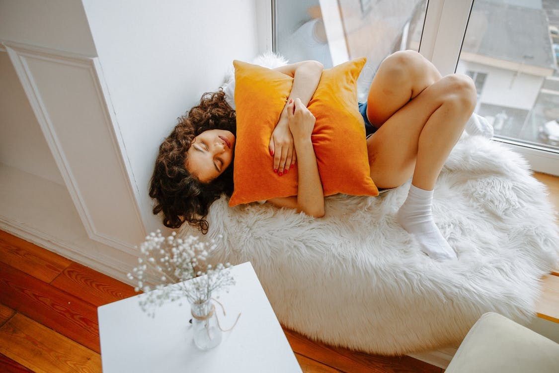 枕をギュッと抱きしめる女性