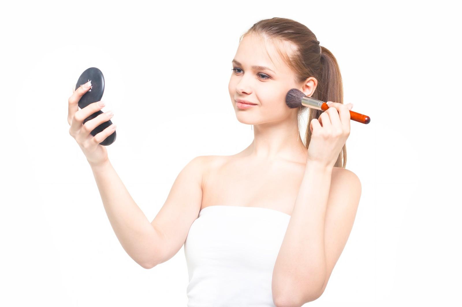鏡を見ながらオーガニックチークを塗る女性