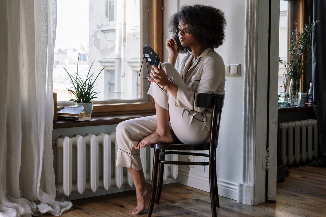 オーガニックパジャマを着ながら携帯を見る女性
