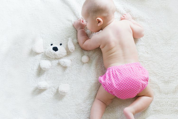 オーガニックのベビーローションを試している赤ちゃん