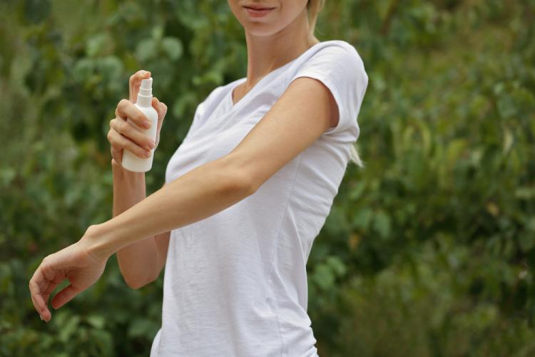 オーガニックの虫除けスプレーを噴霧する女性