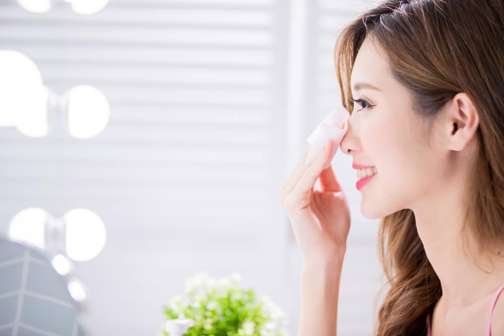 オーガニックのクレンジングオイルで鏡を見ながらクレンジングする女性
