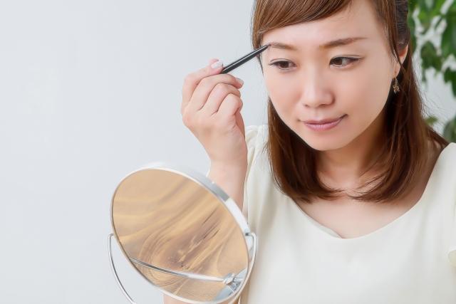 オーガニックアイブロウで鏡を見ながら眉毛を描く女性
