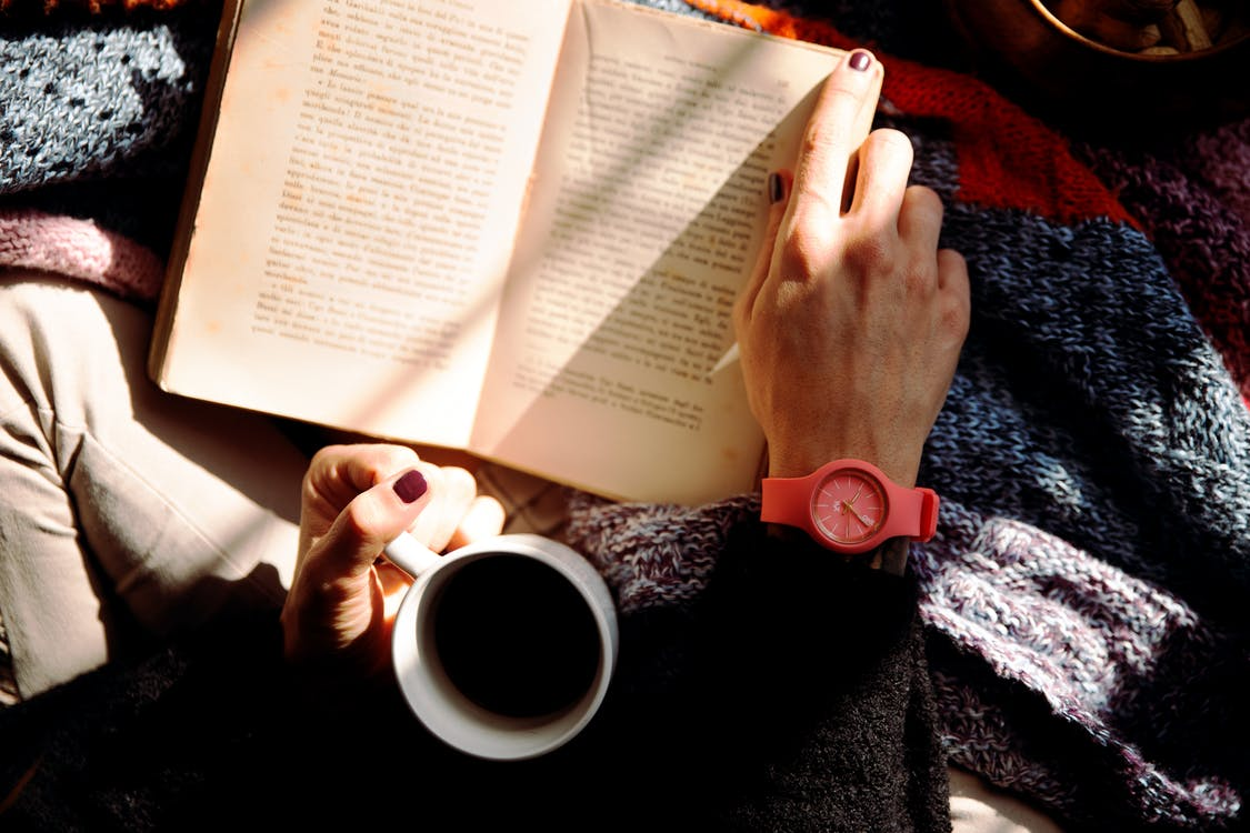 コーヒーを片手に読書をする人
