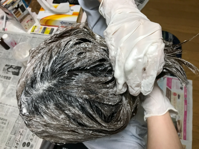 オーガニックのヘアカラーを手袋でする女性