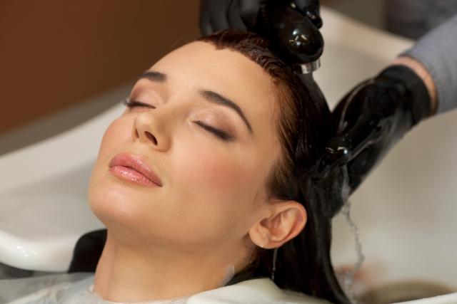 オーガニックのヘアカラー後にシャンプーをされている女性