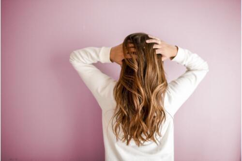 ロングヘアをかき上げる女性の後ろ姿